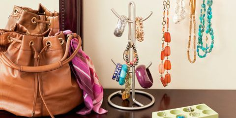 purse, necklaces, rings, bracelets on wooden table