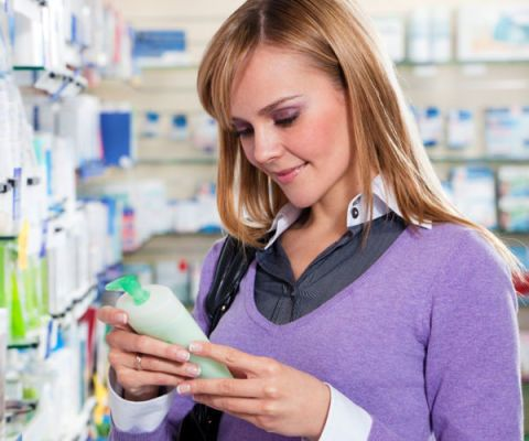 woman reading labels in drugstore