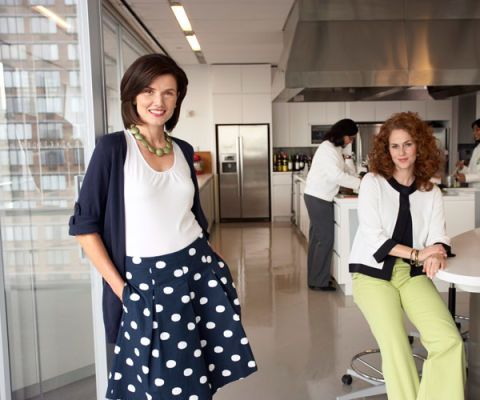 woman styled in spring fashion wearing a polka dot skirt white shirt and long navy sweater with green necklace accessory