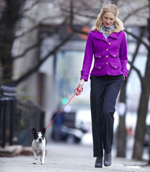 woman woman wearing bright blazer and walking dog