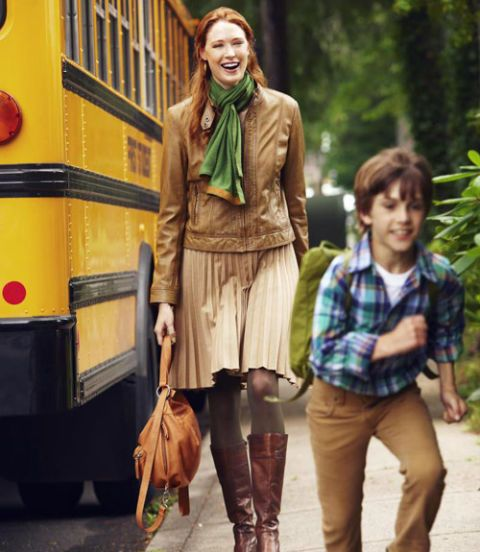 woman in pleated skirt next to school bus