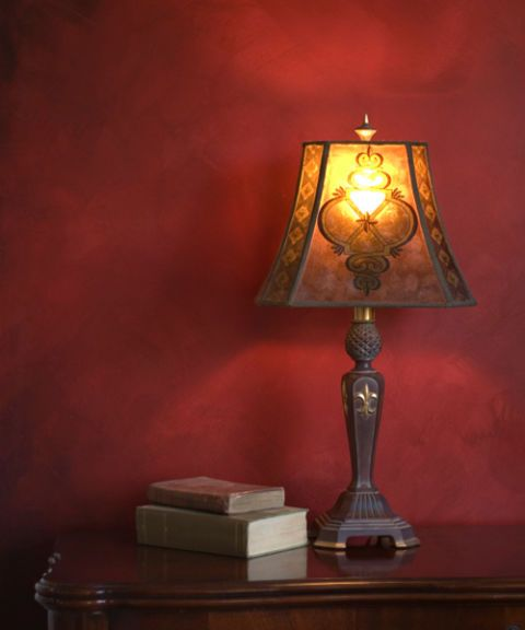 antique lamp on table with books and red wall