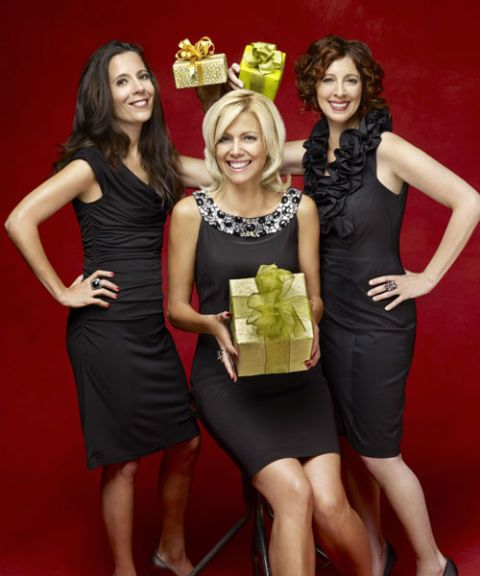 women posing with presents in black dresses
