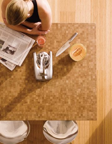 Teragren makes beautiful green countertops out of bamboo, such as this one, shown from above, with a woman reading a paper.