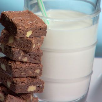 Stack of brownies next to a glass of milk.