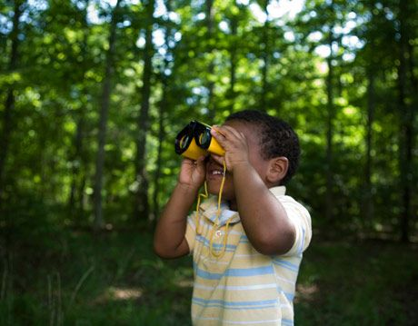 kid in woods with binoculars