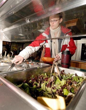 a student at college of the atlantic helps herself to organic salad bar in dining hall