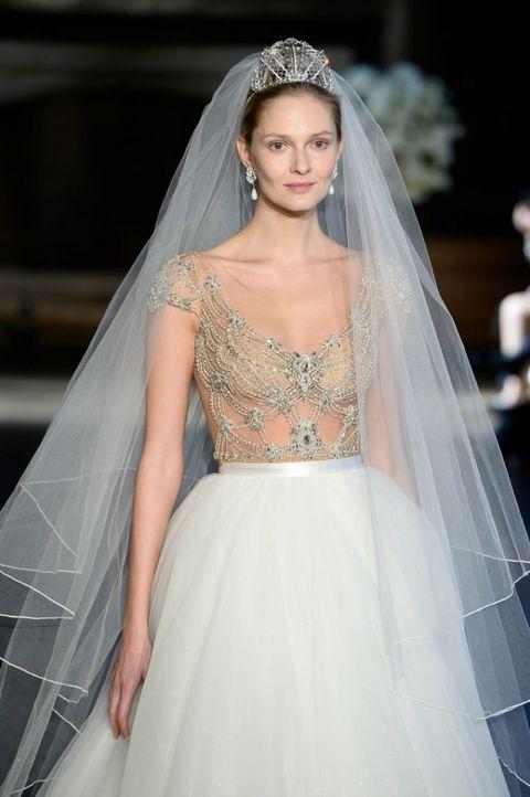 <p>Diadema con pietre preziose che illuminano il volto, dalla corona parte anche il velo, Alon Livne. </p>