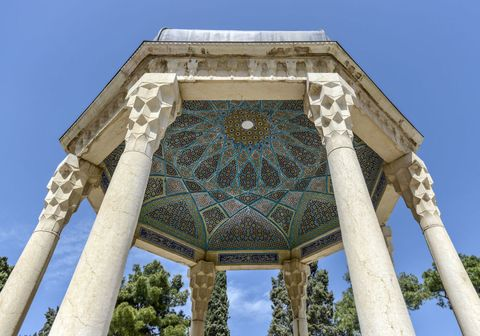 """<p>Nell'Aramgah di Shiraz (nella foto), il """"luogo di riposo"""" di Hafez, chiunque può porre una domanda al destino: all'ingresso un <em>fal-gir</em>, un indovino, tiene tra le mani una scatola piena di bigliettini con i versi del poeta. Un pappagallino, appollaiato sul suo dito, ne sceglie uno con il becco. È il <em>fal</em>, la risposta del fato. Shiraz è così: ammaliante e segreta. Risparmiata dalla distruzione mongola, ha ospitato letterati e architetti contesi dai sultani di tutto il mondo. Per esempio, nel XVII secolo, fu un architetto di Shiraz, Eisa Khan, a progettare il celebre Taj Mahal in India. </p>"""