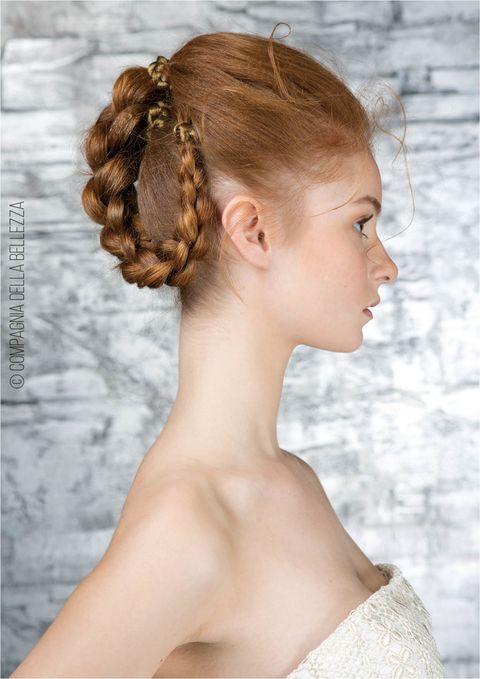 <p>I capelli, cotonati sulla cima del capo, sono ravviati in un pony tail alto, poi intrecciato. L'elastico è ricoperto con piccole trecce di capelli finti mentre la treccia, raccolta da un lato, è fermata con forcine invisibili.</p>