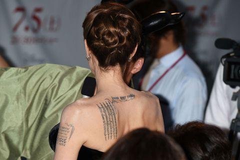 <p>In Thailandia Angelina Jolie si è fatta tatuare cinque righe verticali in lingua Khmer per proteggere i suoi figli, sulla spalla sinistra, mentre più centrale, tra le scapole, è presente la scritta 'know your rights'. Sempre a Bangkok l'attrice si è regalata una tigre del Bengala nella parte bassa della schiena (che copre parzialmente altri disegni), e negli ultimi tempi negli 'spazi vuoti' tra le scapole che vedete nella foto sono comparsi dei nuovi tatuaggi, tre simboli thai e mantra.</p>