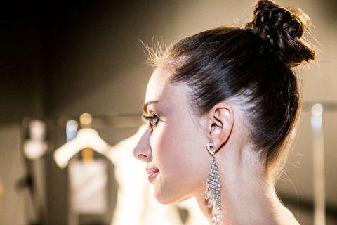 <p>I capelli sono perfettamente ravviati e poi raccolti nello chignon alto, quasi un top knot.</p>
