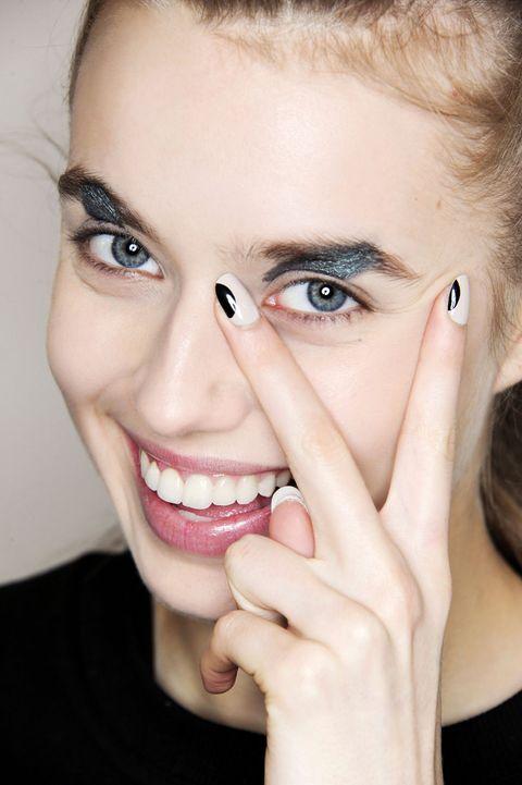 <p><u>Come si fa:</u> questa nail art richiede una mano esperta. Prima si stende la base nera, si lascia asciugare bene, si applica lo stickers ritagliato e poi si stendono due mani di lacca bianca (sfilata Cornejo).</p>