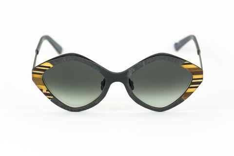 """<p>L'occhiale da sole non può certo passare in secondo piano nel look di una perfetta <a href=""""http://www.elle.com/it/search/fashion%2520icon"""">fashionist</a>, anche in vacanza. Su cosa puntare? Forme e materiali nuovi e di ricerca come il modello romboidale firmato Catuma Thinking, con frontale in ardesia color lavagna e bordura in legno a fantasia geometrica sui toni del marrone, giallo e viola. Le lenti sfumate nere? Un grande classico.<br/></p><ul> <li></li> </ul>"""