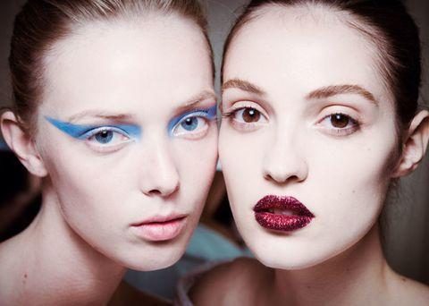 <p><strong>Versace</strong> offre una doppia proposta di ispirazione punk. Labbra glitter o ombretto allungato fino alle tempie. La pelle è invece bianca, appena scolpita da un fard in nuance taupe.</p>