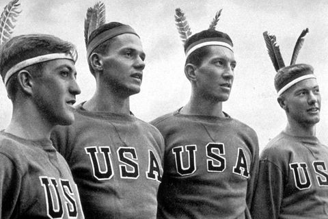 August 1936:  Four American athletes wearing Indian headresses watching their fellow athletes at the 1936 Berlin Olympics.  (Photo by Hulton Archive/Getty Images)