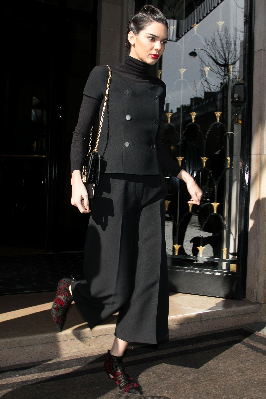 <p>Maglia nera a tartaruga sotto un top con bottoni, abbinati ai pantaloni ampi diZeynep Arçay e agli stivalettirossi e neri, Parigi.</p>