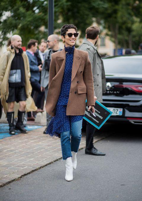 <p>Metti un paio di jeans classici, uno stivaletto bianco e un cappotto (maschile) color cammello. Il tocco di classe assoluta è abbinare al denim un vestito estivo, leggerissimo e corto, che ti farà da top.</p>
