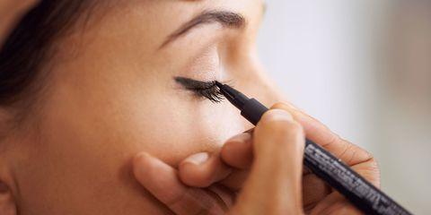 applying eye liner to model