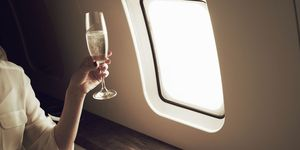 Woman drinking champagne on aeroplane