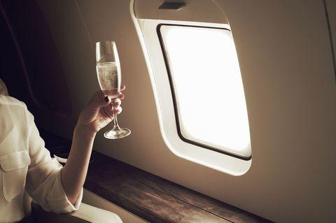 Woman drinking champagne on aeroplane