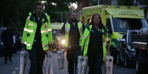Paramedics carry oxygen tanks by Grenfell Tower in West London