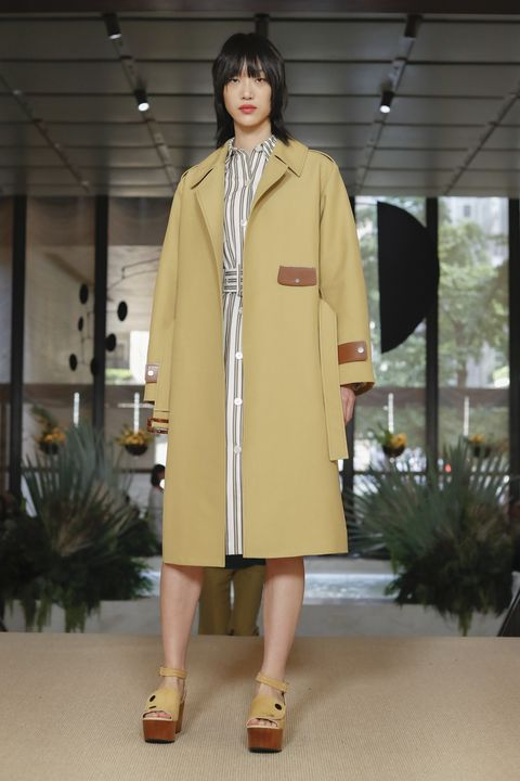 Clothing, Fashion model, Fashion, Overcoat, Coat, Fashion show, Outerwear, Yellow, Trench coat, Fashion design,