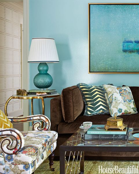 In the living room, Harper re-covered the clients' old sofa in a Duralee brown cotton velvet — a masculine foil for the blue walls. Lee Jofa's Arcadia on Jayson Home's Penelope chair. Lamp, Darnell &amp&#x3B; Company.