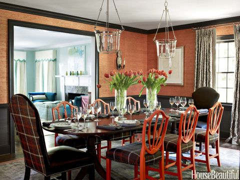 With strong, saturated colors, designer Lindsey Coral Harper boosts the drama in the dining room of this Charlotte, North Carolina, house. Heirloom chairs were refreshed with Benjamin Moore's Oriole and the Romo Group's Dulcie plaid. Schumacher's embroidered Amboise linen curtains add soft grays and silvers. The grass cloth on the walls is Phillip Jeffries's Extra Fine Arrowroot.  <strong>HB's Paint Picks:</strong> Oriole, Midsummer Night, and Antiguan Sky, all by Benjamin Moore.