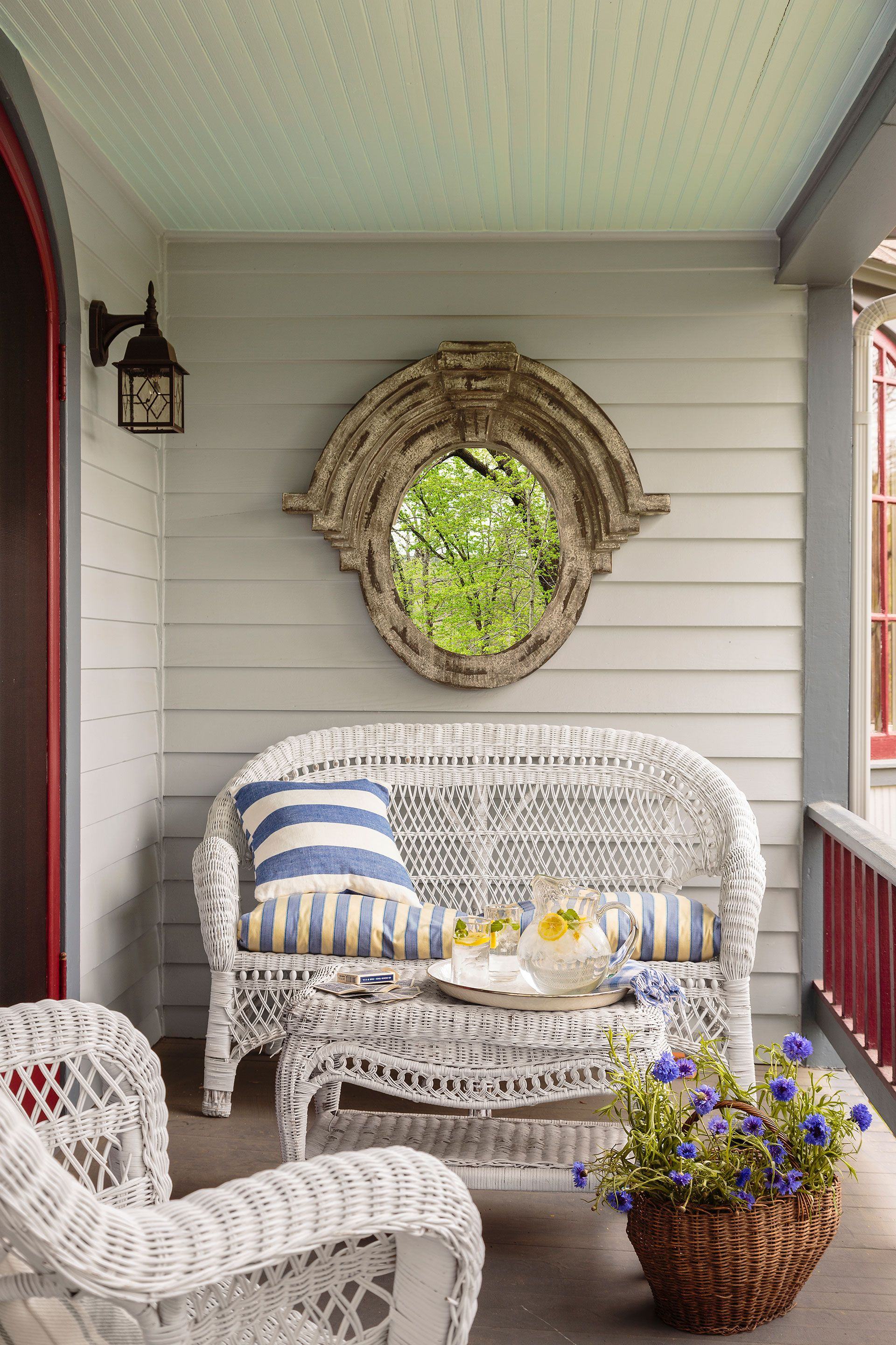 Vintage style white wicker furniture on a front porch with dramatic Old World mirror. #frontporch #decoratingideas #wicker #furniture