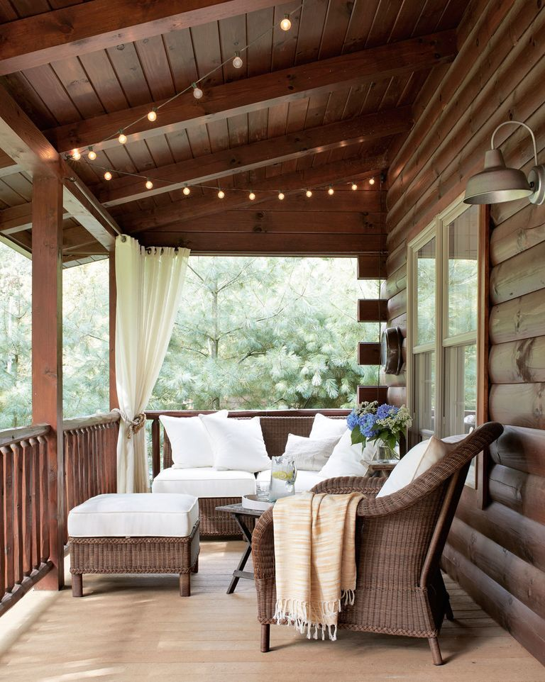 Wicker furniture, white cushions, and rustic dark wood combine for a cozy cabin porch strrung with white lights. #porch #cabin #cozy #decoratingideas