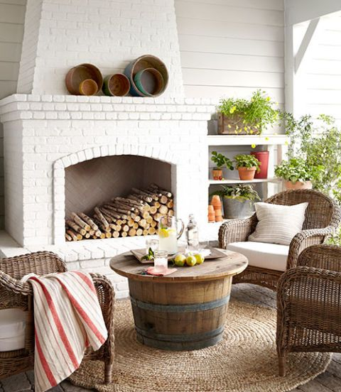 The combination of California weather and a fireplace makes this outdoor living area a year-round hangout. Wicker chairs from a local shop surround the coffee table, fashioned out of a reclaimed wine barrel. The walls are painted Sherwin Williams Collonade Gray. Fireplace is painted Benjamin Moore China White. #outdoor #fireplace #decoratingideas