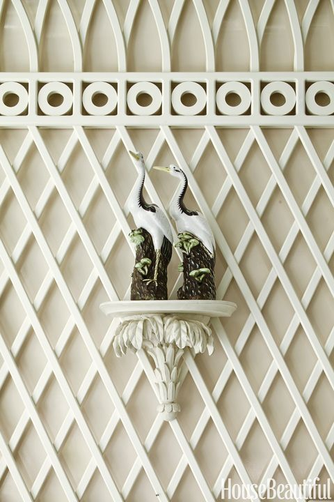 A pair of porcelain egrets perch on a palm wall bracket.