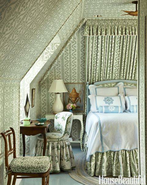 An attic guest room is Kincaid's homage to legendary designer Sister Parish, whose classic Dolly fabric makes the tiny space feel as fresh as a spring meadow. A John Rosselli bedside table holds a Christopher Spitzmiller lamp. Bedding, Leontine Linens. Floor painted in Farrow & Ball's Dix Blue.