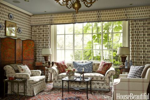 For coziness and an Anglo-Indian flavor, Kincaid swathed the family room in Robert Kime's Field Poppy, a print based on a textile found in Jaipur, India. The large-scale striped Avignon Red by Kime on a club chair from George Cameron Nash contrasts with the discreet florals, Kaveri and Bhavani by Nicholas Herbert, on a custom sofa and chair.