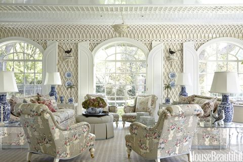Fanciful treillage adds another level of lovely detail to the sunroom. Huge arched windows bring big blasts of light into the space, where the homeowners do most of their entertaining. The sofas and chairs, by custom furniture firm DeAngelis, are upholstered in Robert Kime's Jardinieres. Custom ottoman in Claremont's Serge Antique. Temple jar lamps, John Rosselli. Elizabeth Eakins rug.