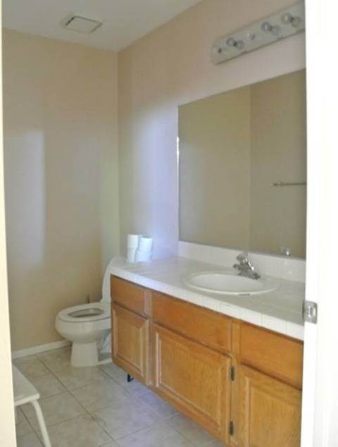 "This standard-issue bathroom with a rectangular mirror, beige walls, simple countertop, and honey-colored wood in blogger <a target=""_blank"" href=""http://www.centsationalgirl.com/"">Centsational Girl</a>'s home lacked personality."