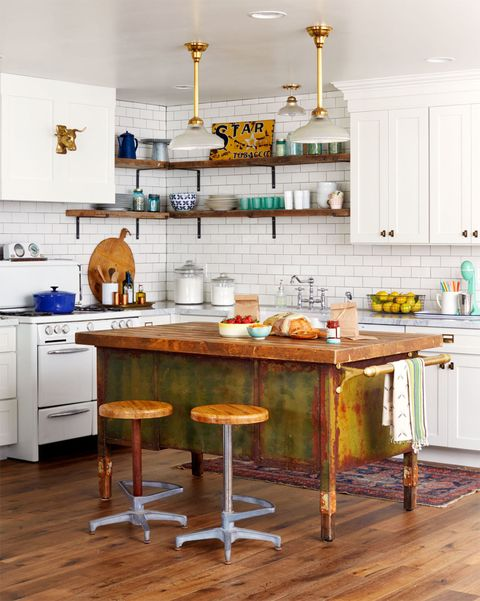 """<strong>The find: </strong>A wood and metal military desk-turned-prep island ($650) that Coley bought from one of her market vendors.  <strong> How it makes the room:</strong> The weathered wood top and rusty green base give Coley's all-white, freshly renovated kitchen more personality. """"New spaces need a little old soul,"""" says Coley. """"I love to think about its previous life, where it's been, and what it meant to someone."""" Barnwood shelves pick up the warmth of the island's counter, while brass pendants (from an old ice-cream parlor) echo the towel bar's shine."""