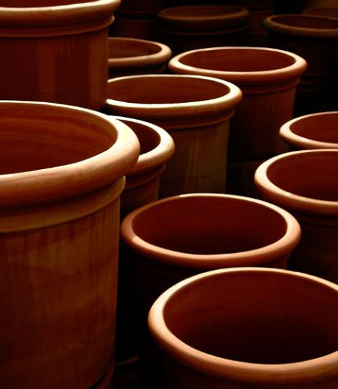 <p>Scour pots with a stiff-bristled brush and rinse. Try to find one with a solid-wood handle and palm fibers. </p>