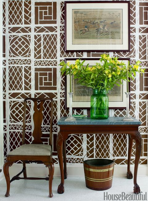 In the dining room, the homeowner's equestrian prints hang on walls papered in Lyford Trellis, a graphic bamboo lattice print by China Seas that brings a touch of the garden inside. The granite-topped mahogany console table and brass-mounted peat bucket came from a Christie's auction.