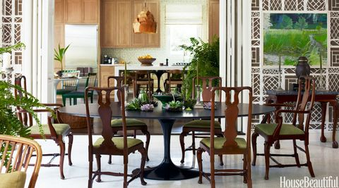 <p>A black Saarinen dining table by Knoll offers a sleek contrast to traditional Queen Anne-style chairs. Folding panel doors reveal the kitchen beyond, where Scheerer fashioned an island with a mirrored kneehole that gives the illusion of a huge Parsons-style table while concealing cabinets and appliances. The pendant is by Ingo Maurer.</p>