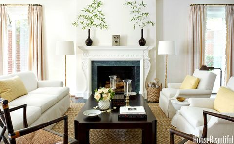 <p>Using little color, no pattern, and a wealth of textures, designer Tom Scheerer composed a chic, crisply edited living room to set the scene. Armchairs and custom sofa are in Perennials' Raffia, while the vintage coffee table is by Michael Taylor. The pair of floor lamps are courtesy of Arteriors. The walls are in a high-gloss ivory by Fine Paints of Europe, and the softsisal rug is from Blackstone Carpets. </p>