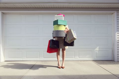 Woman holding boxes and bags of shopping