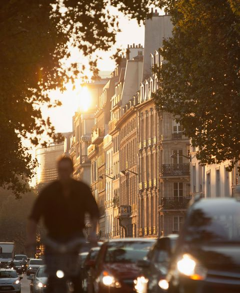 The busy, early morning commute passes the iconic Haussmann architecture at dawn in Paris, France
