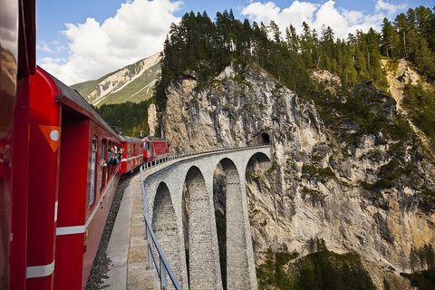Transport, Highland, Mountain, Railway, Rolling stock, Bridge, Arch bridge, Mountain range, Travel, Train,