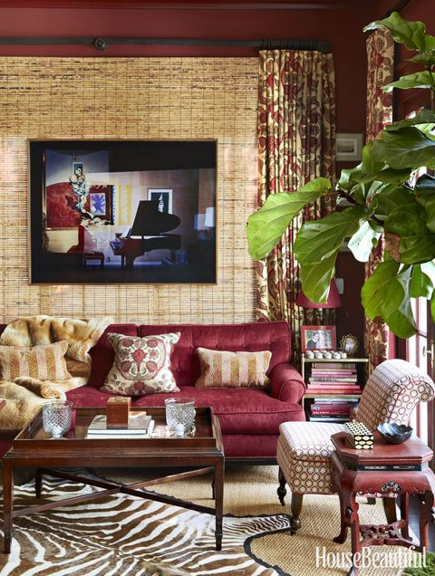 """Nothing transports like a deep red room,"" says McDonald of the sumptuous library. The window was covered with a bamboo shade to create an artful backdrop for the photograph by Augusta Wood. Walls in Benjamin Moore's Classic Burgundy. A Vaughan side table holds a lamp by Visual Comfort; a zebra-patterned hide tops a Stark rug."