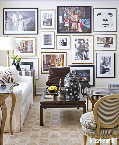 <p>A gallery wall in the living room showcases some of Alessandro Uzielli's photography collection. Coffee table, Vaughan. Side table, Minton-Spidell. The striped chair is a Paris flea market find.</p>