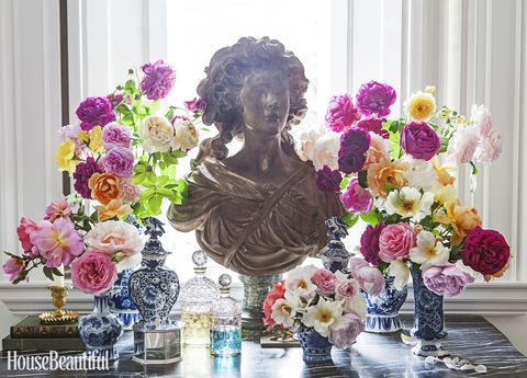 console table with a display of a bust and flowers