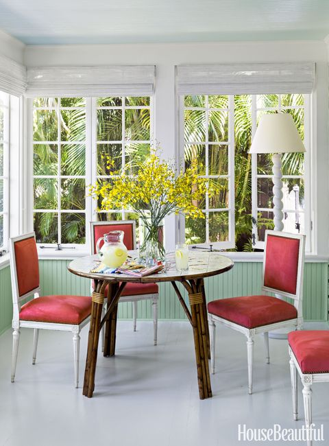 todd romano florida house dining room with red chairs and rattan table