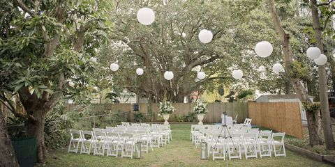 outdoor wedding ceremony with empty white chairs